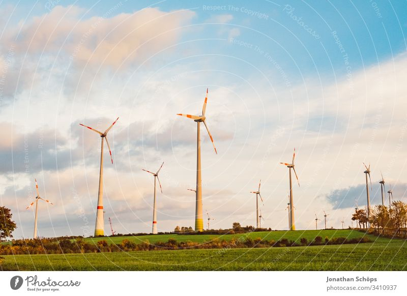 ecological renewable green energy wind power station on a field in evening sun alternative background blue change clean climate change cloud countryside design