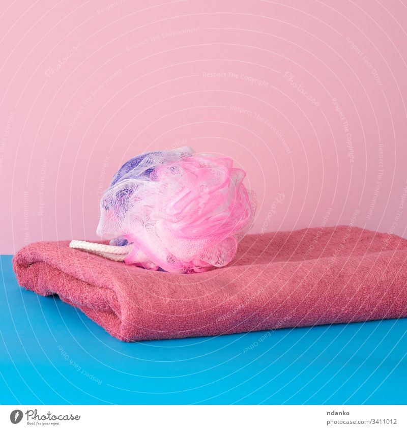 stack of pink folded towels and a plastic washcloth on a blue background bath bathroom beauty body bright care clean closeup color colorful cotton domestic dry