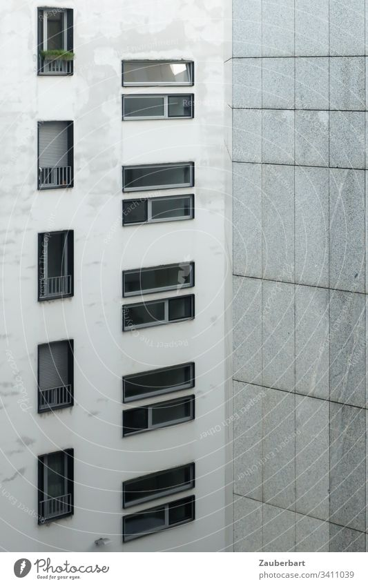 Facade of a high-rise building with windows in portrait and landscape format and granite slabs in light grey High-rise House (Residential Structure)