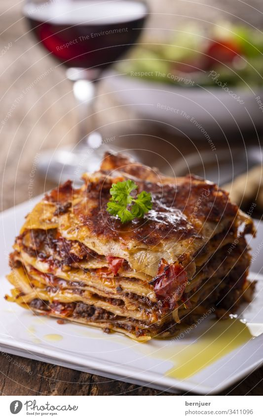 Lasagne on a plate Red wine Lettuce grissini Summer Vine White Wood Rustic Minced meat herbaceous Bolognese Bolognaise Crockery Mixed Tasty Mozzarella Portion