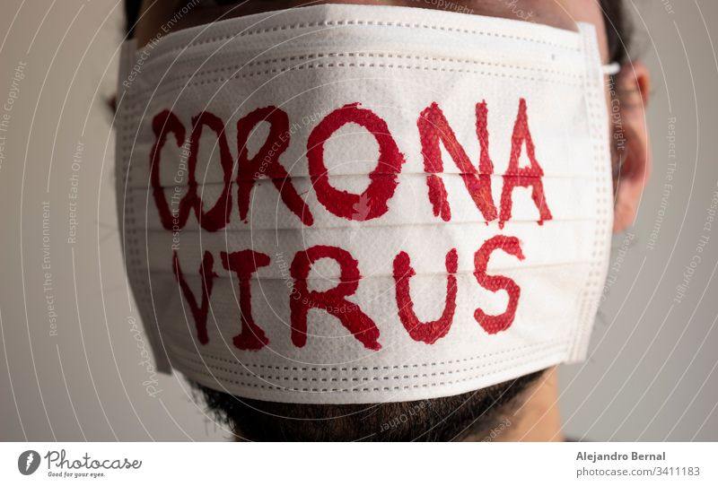 Closed up to a CORONAVIRUS man patient with beard using a white face mask with red CORONAVIRUS inscription. Concept photography COVID-2019 2019-ncov alert