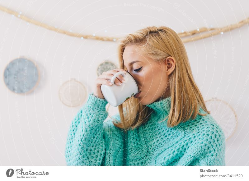 Young pretty girl  drinking coffee woman tea young cup sweaters blonde morning portrait happy beautiful female wall dreamcatcher sunday women home lifestyle