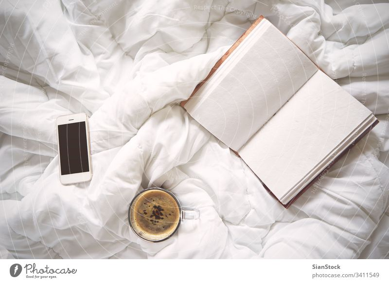 Cup of coffee, vintage notebook and smartphone on bed, white laptop cup morning blanket home room bedroom light beautiful lights isolated background lifestyle