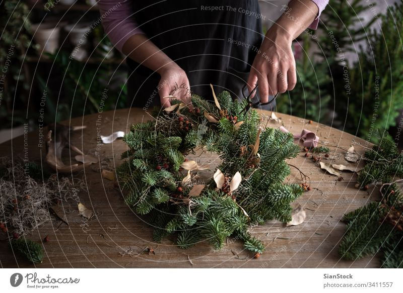 Woman making Christmas wreath of spruce, step by step. Concept of florist's work before the Christmas holidays. hand woman hands wooden table handicraft