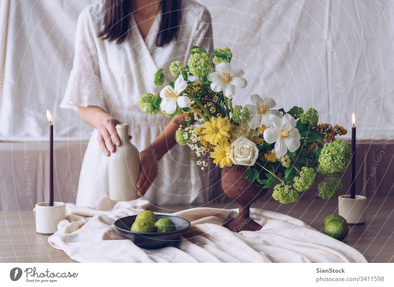Woman holding bottle. Still life with flower concept flowers table woman young caucasian hands dress white vase brunette candles lime bouquet decoration