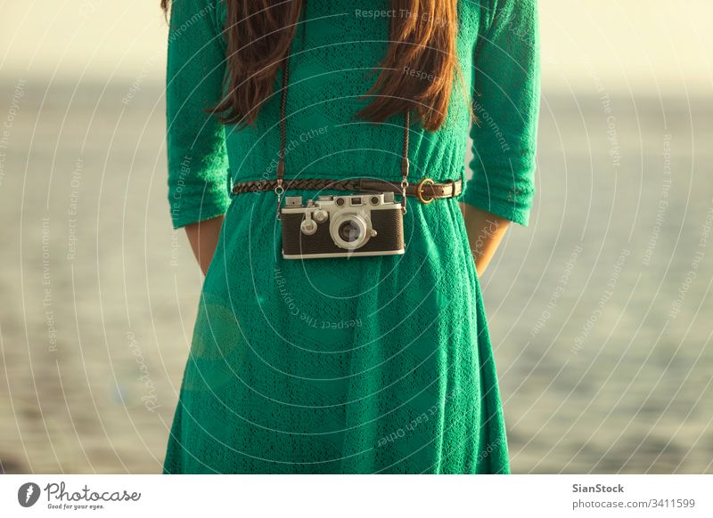 Vintage photo, brunette girl with retro camera beach vintage ocean vacation people summer travel blue photographer fashion lifestyle holiday funky women