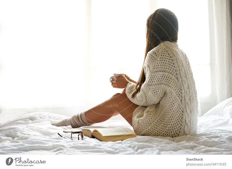 Soft photo of a woman on the bed with an old book and a cup of coffee Bed Woman Reading Window view lazy Sunday Winter Coffee Cup Tea Morning Girl Home