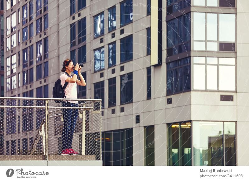 Female photographer takes pictures of architecture in New York. woman camera city urban creative sightseeing photojournalism journalist caucasian brunette