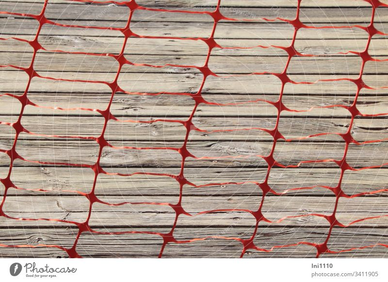 Foil tape red punched out as grid blocks passage to the grey wooden bar Packing film plastic Plastic film punching cordon Warn No trespassing peril Fence esteem