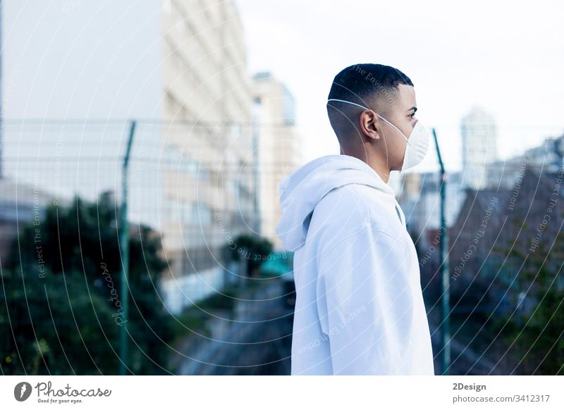 Side view of a young male wearing protective facial mask against transmissible infectious diseases and as protection against the flu or coronavirus in public place.