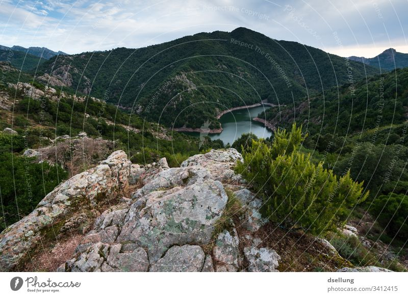 View of lake and green mountains with rocks in the foreground Vantage point Green Forest Bushes Sky Clouds Mountain Hill Landscape Nature Tree Grass Meadow