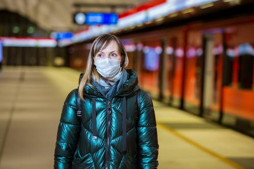 Woman in winter coat with protective mask on face standing on metro station, waiting for train, looking worried. Preventive measures in public places of epidemic regions. Finland, Espoo