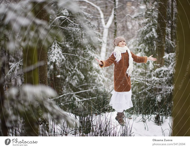 A 7 year old girl in a brown sheepskin coat walks in the forest. Concept of the seasons, a winter fairy tale. Snow, trees. baby background beautiful beauty blue