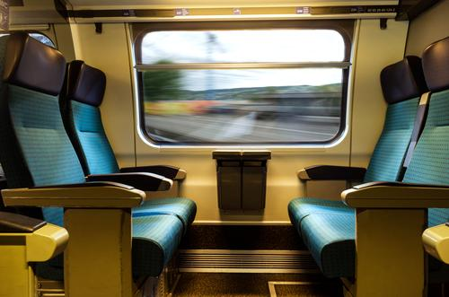 Moving train four empty coach seat blue upholstery swiss sbb rail network window travel comfortable transportation inside journey business horizontal speed