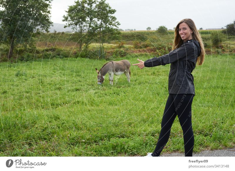 Young woman with a donkey on a grass field farm outdoors food offspring mammal feeding look farm animal cute nature rest green eating head mule face adorable