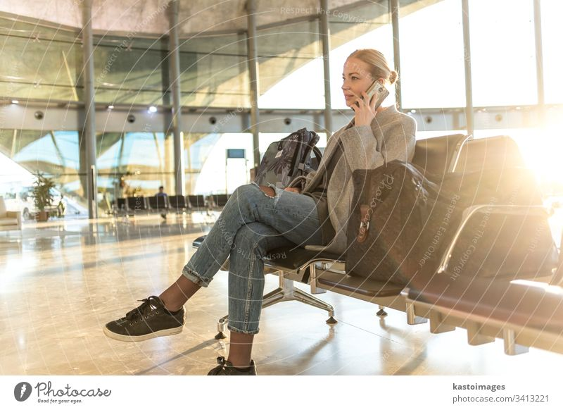 Female traveler talking on her cell phone while waiting to board a plane at departure gates at airport terminal. female woman business flight baggage luggage