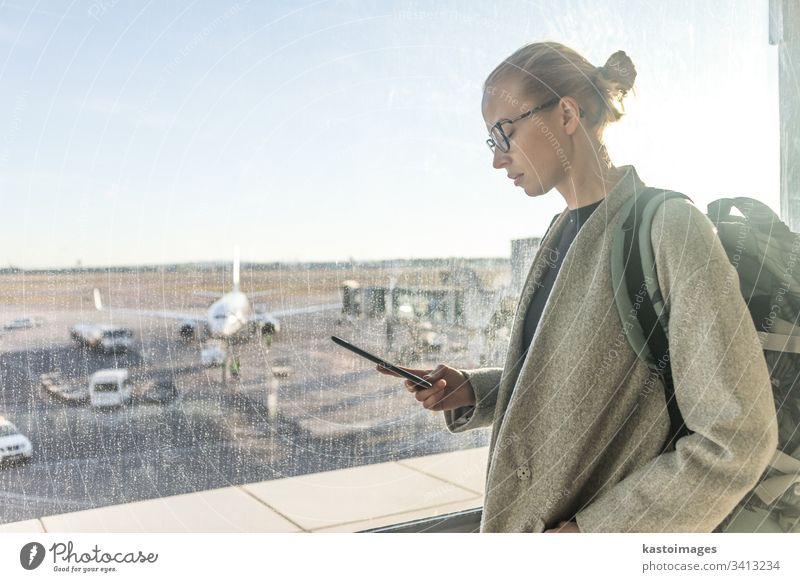 Casually dressed female traveler at airport looking at smart phone device in front of airport gate windows overlooking planes on airport runway woman girl