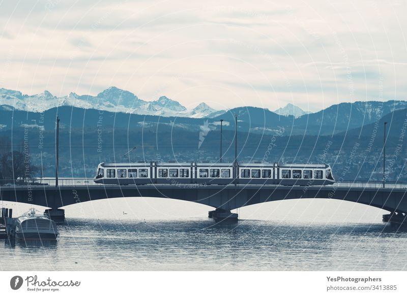 Tram in Zurich on bridge over lake. Mountain skyline Switzerland blue hour city tour duotone europe european landscape monochrome morning mountain range