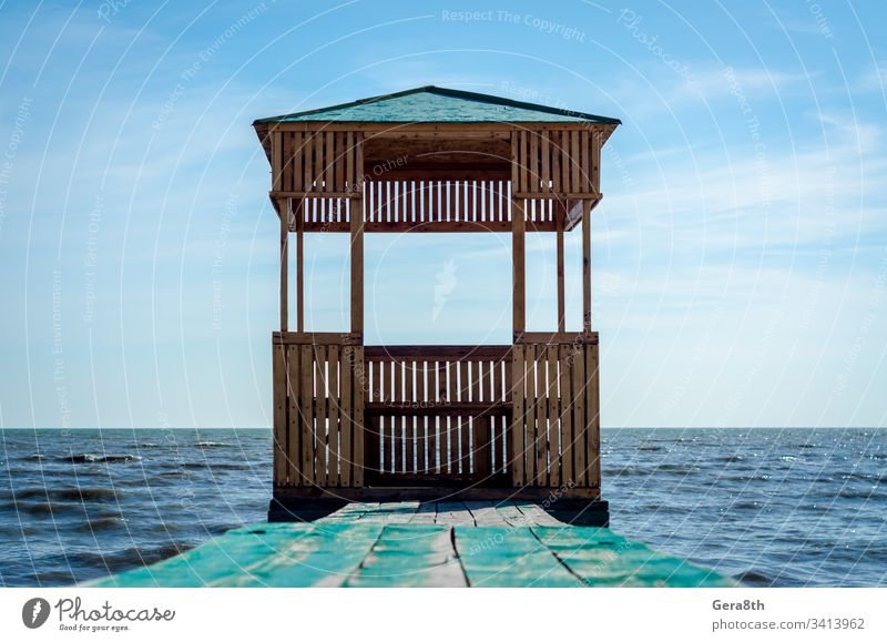 wooden arbor on the background of the sea and blue sky with clouds boards building gazebo nature old painted roof seascape surface water waves wooden gazebo