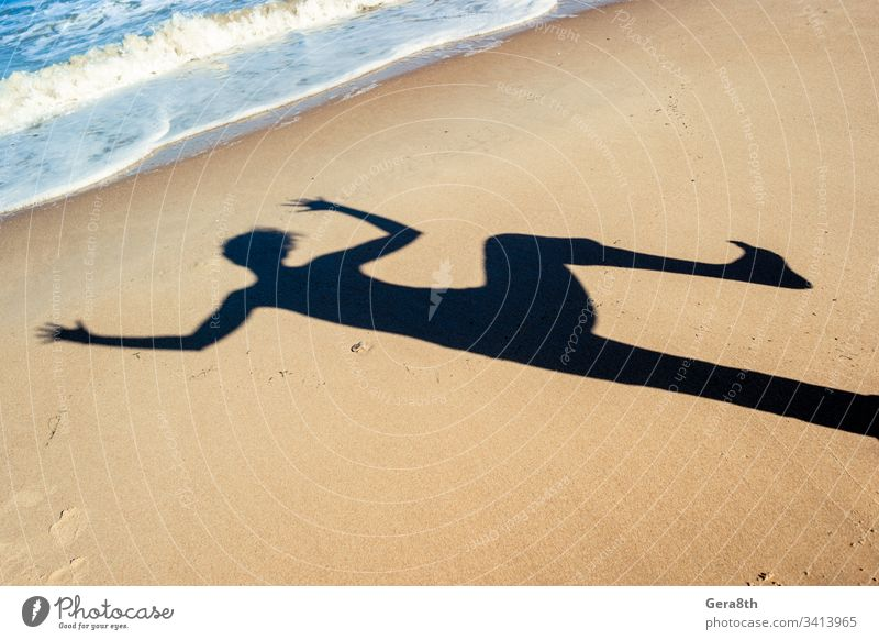 shadow of a dancing girl on the sea sand on the beach near the sea black blue dancing shadow hands rest shadow of a girl shadow of a woman shadow on the sand