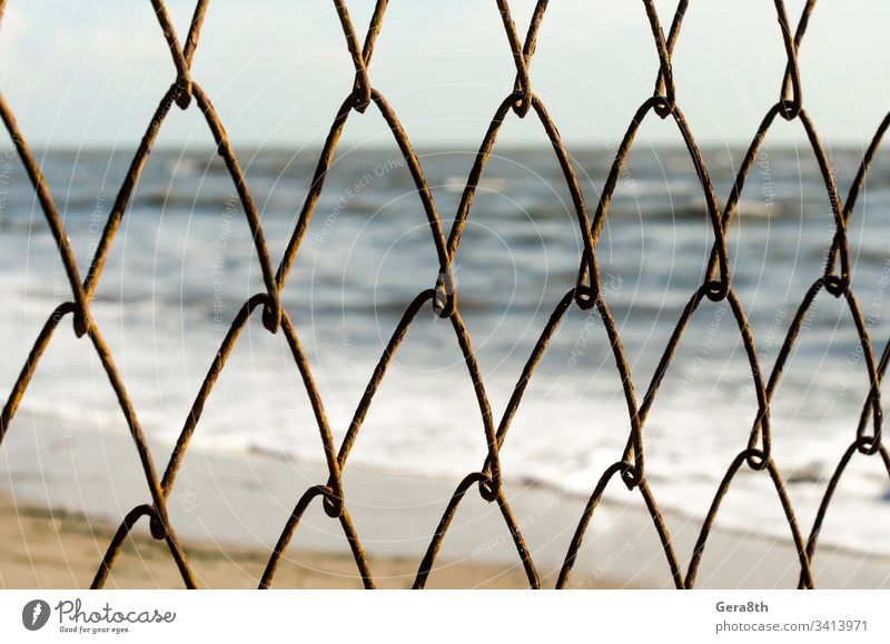 mesh wire fence on the background of the beach and the sea abstract blur blurred nature ocean repeating rust rusty sand sky surf water waves