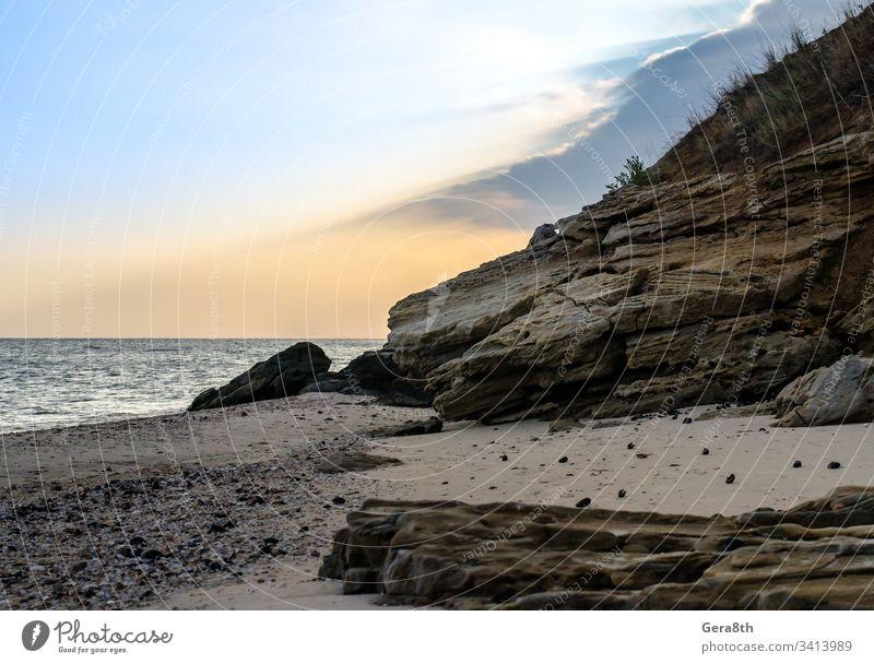 rocky seashore against the evening sky beach clouds horizon nature ocean rocks rocky shore sand seascape season stones summer sun rays sunset