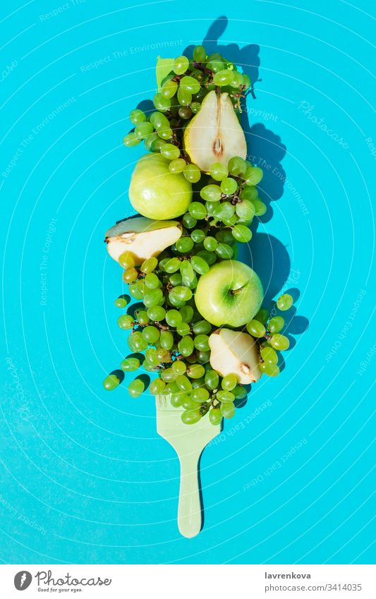 Composition with ripe grapes, pears, apples and brush colored green on blue background diet vegetarian fresh ingredient spring organic food plant colorful