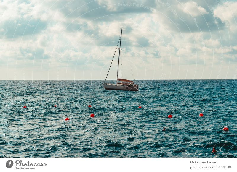 Small sail boat drifting alone in the mediterranean sea Liguria Italy on a overcast summer day adriatic adventure blue clouds coast europe freedom hobby holiday