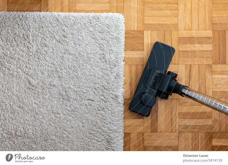 Vacuum cleaner extension on a laminated wooden floor next to a grey fabric rug gear rugs textile close-up pure place area maintenance photography hoover