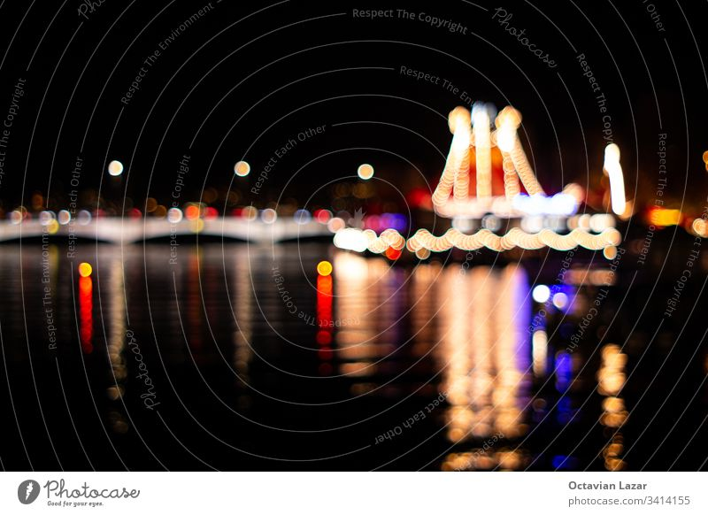 Out of focus night landscape of Zurich city light from the Limmat river side illuminating Christmas lights bokeh circles reflected in the water festive shine