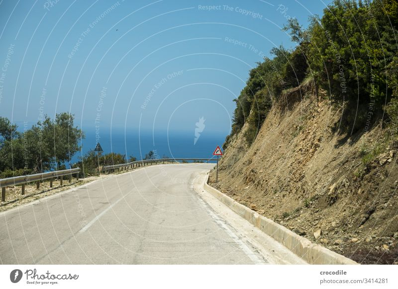 winding coastal road in Albania that branches off to the right Street Coast Right Curve Signs and labeling Concrete Old Ocean road trip bushes Asphalt Line