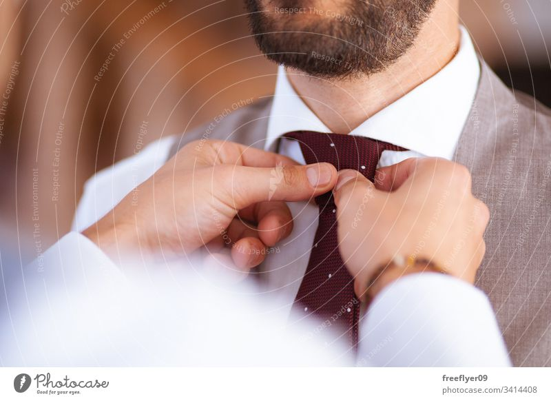 Closeup of two hands helping with the tie to a groom at his wedding suit person male decoration day vest happy floral blooming bow flower closeup engagement