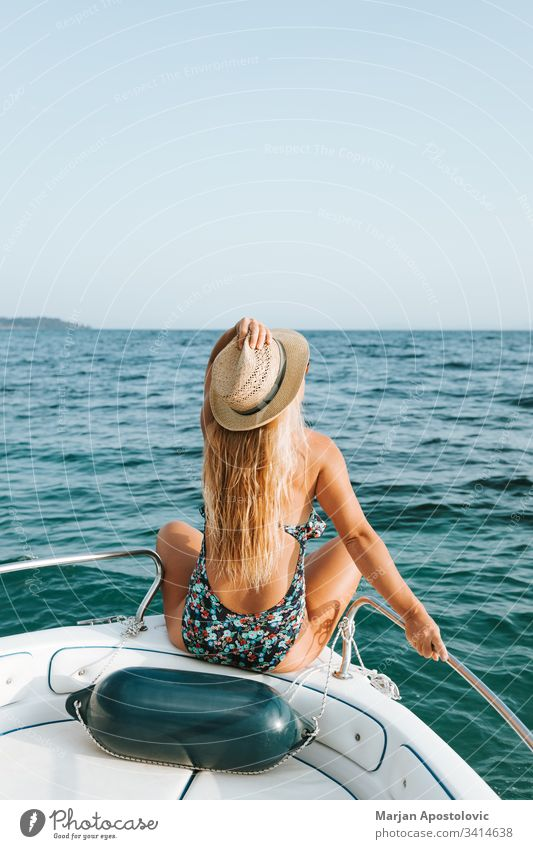 Young woman enjoying on the deck of a boat at the sea adventure attractive beautiful beauty blue caucasian cruise enjoyment fashion female fun girl gorgeous