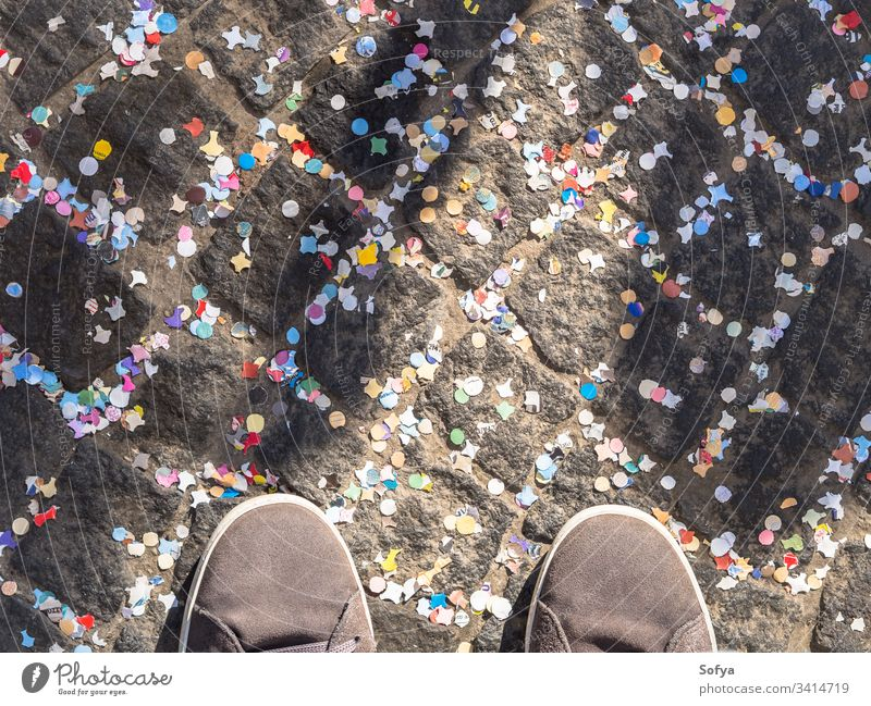 Pavement covered with colorful confetti and shoes carnival celebrate road street texture abstract holiday pavement street photography urban celebration detail