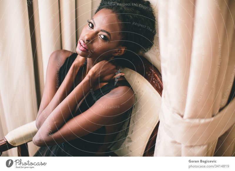 Young black woman in the room afro ethnicity calm adult sit female girl home american charming chair leisure attractive serenity curly relaxing cute modern