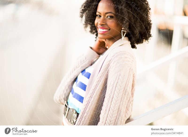 Young black woman on the street ethnicity calm day adult sunny female afro girl outdoors american charming leisure attractive curly relaxing cute modern