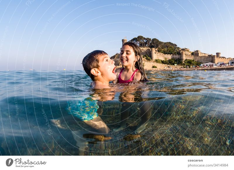 Two little kids playing into the sea active beach beautiful blue boy boys child childhood children cute emotional enjoy excited face family fresh fun happiness