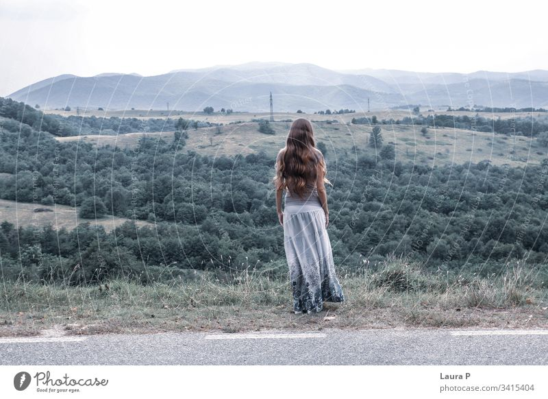 Lonely woman with long hair looking at a hill carefree believe spirit thoughts wind dream day background grass adult horizon person think stress quiet view
