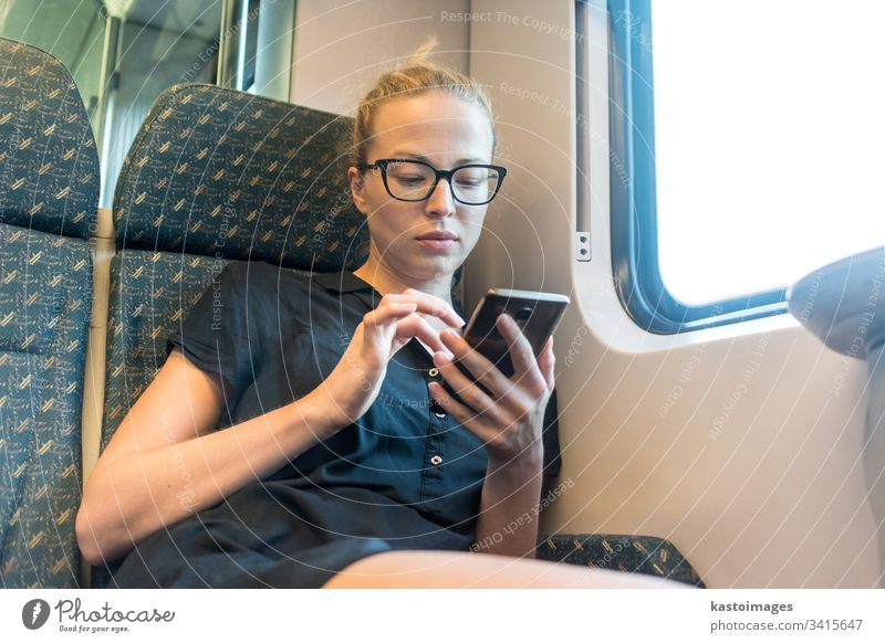 Caucasian female traveler using mobile phone applications while traveling by train. woman transport young passenger smart lady happy trip cellphone
