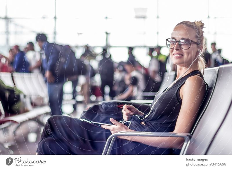 Female traveler using her cell phone while waiting to board a plane at departure gates at asian airport terminal. woman flight young girl destination trip