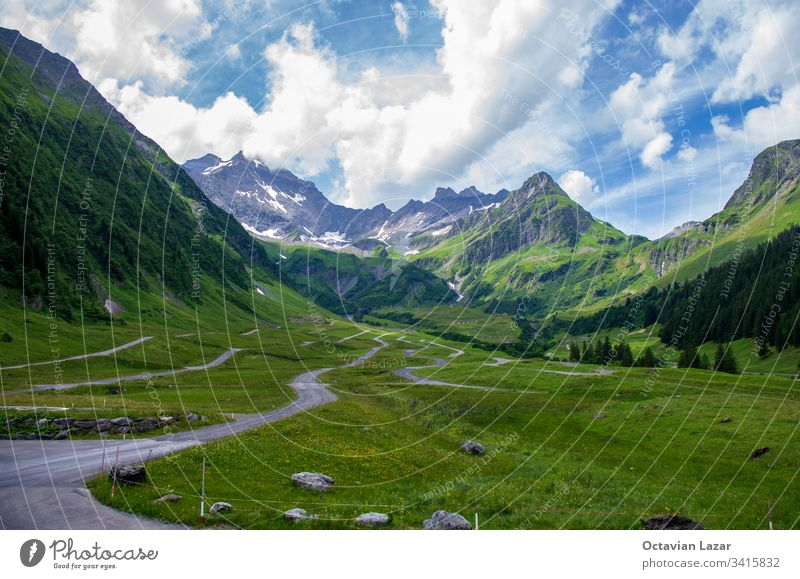 Swiss mountain landscape green grass, blue sky, white clouds, summer day, paved paths nature beautiful travel meadow scenery view valley mountains rock outdoor