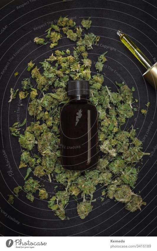 Mountain of marijuana buds with a bottle of CBD make with cannabis on top isolated on black background. CBD or cannabidiol product. cbd Cannabidiol oil weed