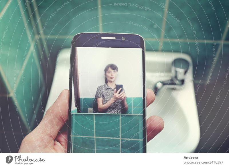 In front of a sink in a turquoise tiled bathroom, a left hand holds a mobile phone with a selfie of a woman smartphone Selfie photo Woman tiles Sink by hand