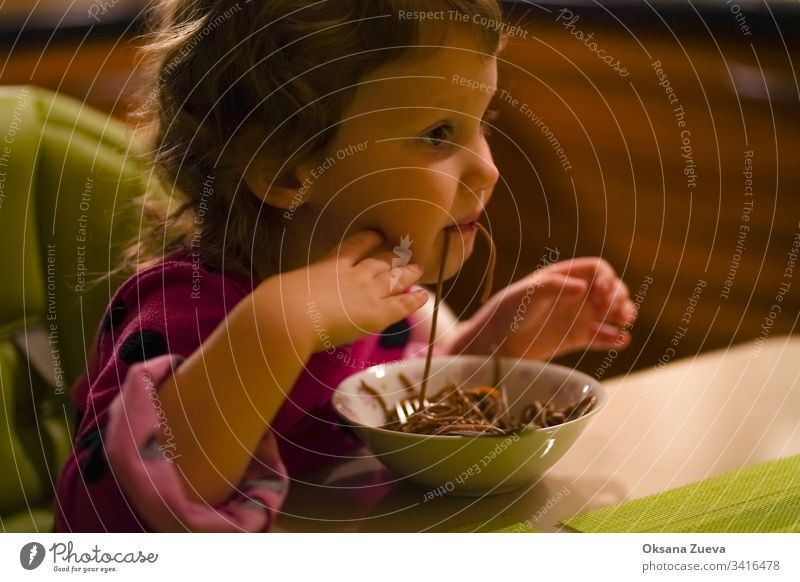 Curly little girl with an appetite eats buckwheat noodles, spaghetti. The concept of good appetite, delicious homemade food. adorable baby black blue childhood