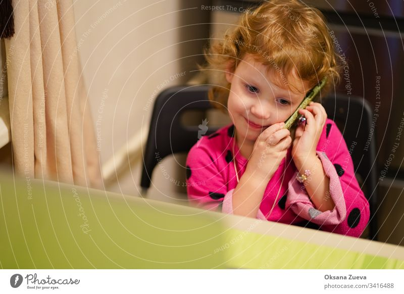 Curly little girl talking with her grandmother on the phone. She smiles, tells the news how she is doing. adorable attractive baby beautiful candid cheerful