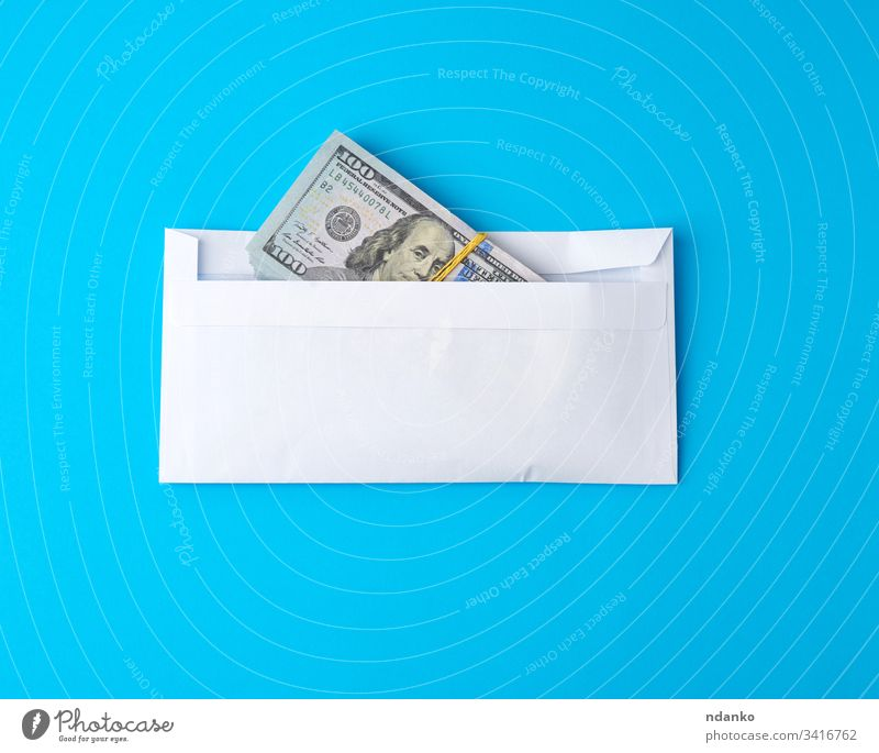 pack of paper American one hundred dollar bills tied with an elastic band and lies in a white envelope money business finance background currency cash bank