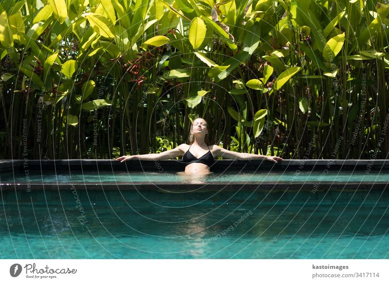 Sensual young woman relaxing in outdoor spa infinity swimming pool surrounded with lush tropical greenery of Ubud, Bali. wellness water nature beauty beautiful