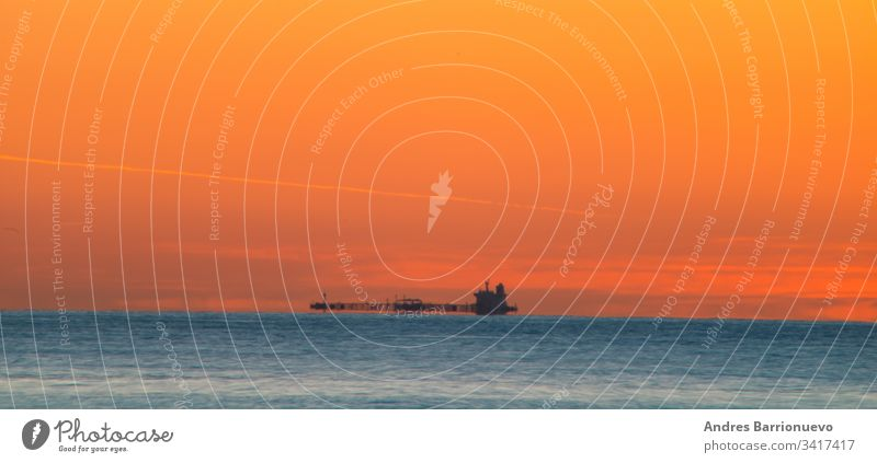 Freighter sailing at dawn travel horizon boat water nobody sea orange transportation cargo landscape ship shipping silhouette evening industrial commercial