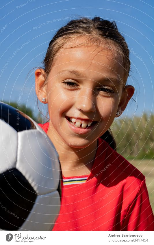 Little girl playing child little one soccer ball youth smile outside young grass kids hands on hips vertical outdoor selective focus uniform green caucasian