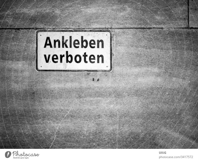 "German prohibition sign saying ""Ankleben verboten"" - No sticking allowed"", amusingly stuck to a stone wall, with copy space. text interdiction forbidden"